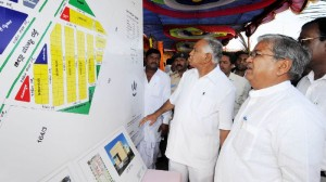 Chief Minister B S Yeddyurappa viewing plan of rehabilated Kotyal Village in Bijapura Dist.Shivaratri Deshikendra Swamiji & Siddeshvara Swamiji,MLA M B Patil,Appu Pattana Shetty seen in pic