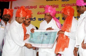 Seven Lakh Rupees Cheque handed by Khanapura MLA Prahlad Ramane to Chief Minister B S Yeddyurappa for CM calamity relief fund Dist Minister Basavaraj Bommai,Cooperation Minister Laxman Savadi seen in pic