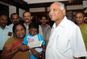 Chief minister B S Yeddyurappa presented Rs 1  lakh cheque to the Smt Mala resident of university campus for Taking care of orpanage child ( Master Srinivas)