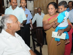 Chief minister B S Yeddyurappa presented Rs 1  lakh cheque to the Smt Mala resident of university campus for Taking care of orphanage child ( Master Srinivas)
